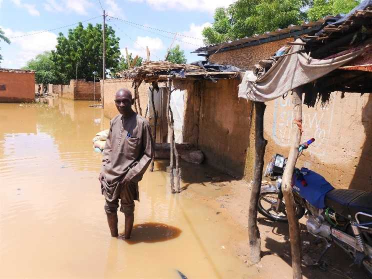 Mr. Belko Idi wades through stagnant water to enter his house. Kirkissoye, Niamey. 4 September 2020. Credit: OCHA/Abdoulaye Hamani