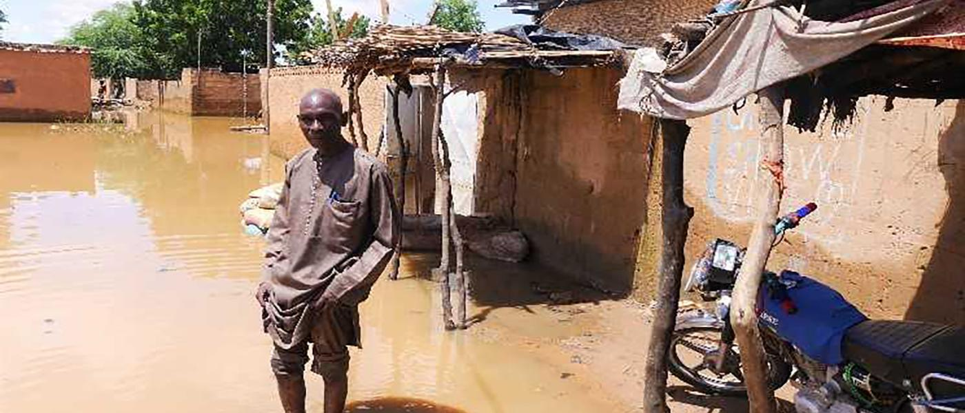 Belko Idi wades through stagnant water to enter his house in Kirkissoye, Niamey, Niger, 4 September 2020. Credit: OCHA/Abdoulaye Hamani