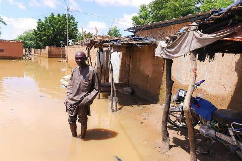 Belko Idi wades through stagnant water to enter his house in Kirkissoye, Niamey, Niger, 4 September 2020.